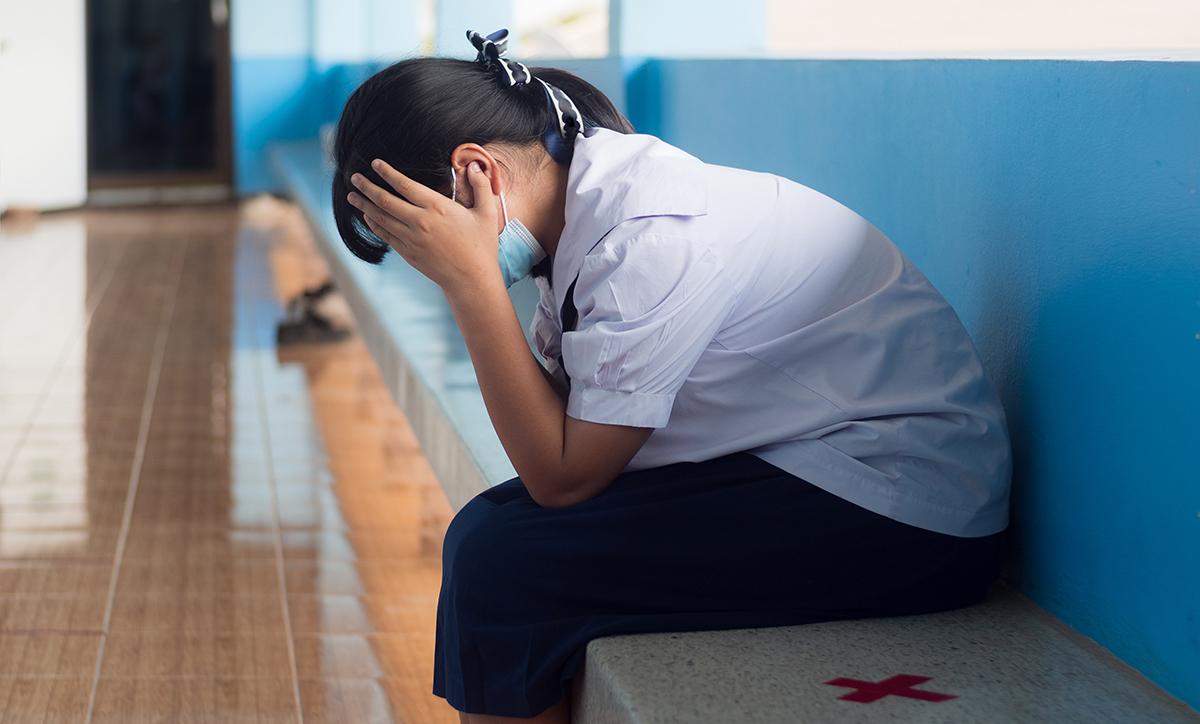 Asian young girl student sitting alone with sad feeling at school
